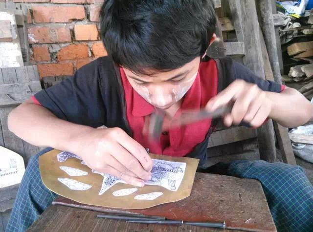 """缅甸顶级手工艺品制作过程 2015-01-20 醉美缅甸  这是缅甸顶级手工艺品的个制作过程的   先是画画,先画一个图案  把画好的图案贴在铜板上。  工匠用锤子、铳子等工具,按照铜板上的图案,敲打成初步的凹凸感。  另外的一个工匠,按图案的线条把图案的突出部分敲打出来。使得铜板变得更加立体。   这种黑乎乎的天然树脂,是从缅甸特有的一种叫樱井树上弄下来的,英文INGIN""""。 这种树脂虽然黑乎乎的,但是一点也不难闻,有一股树木清香的味道。 在佛经里说樱井,就是当年佛出生的时候在这树下出生的。"""